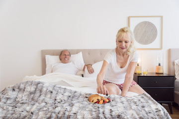 Caucasian woman eating breakfast in bed