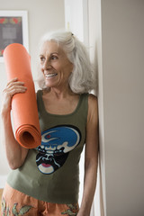 Older woman leaning on wall holding exercise mat
