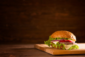 Burger on a wooden board on wooden table over dark background