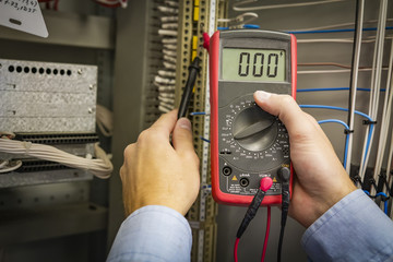 Multimeter in hands of electrician engineer closeup on electric panel background. Test circuit. Service work.