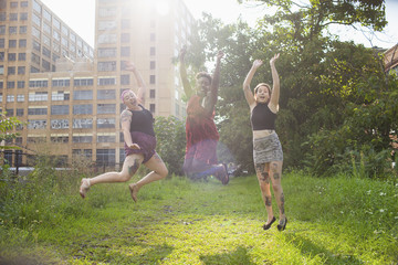 Happy friends jumping in the park