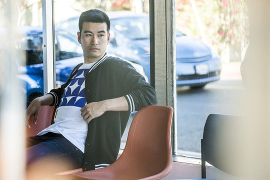 Serious Chinese man sitting in chair near window