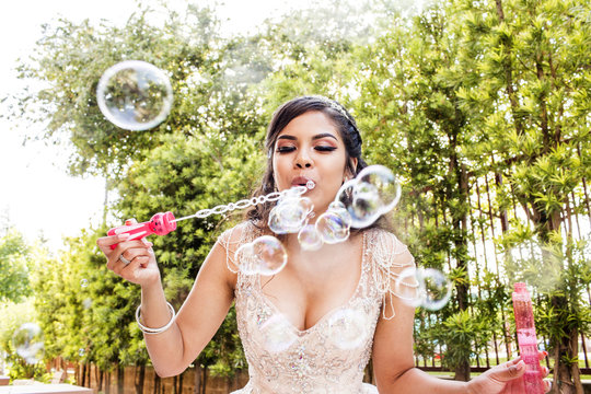 Hispanic girl wearing gown blowing bubbles