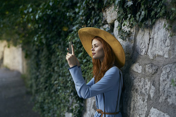 Woman photographing with cell phone near stone wall