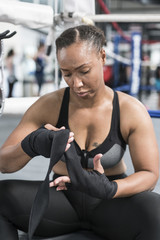 Black woman wrapping hand in gymnasium