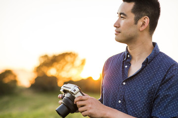 Smiling Chinese man holding camera in field