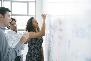 Businesswoman writing on whiteboard in meeting