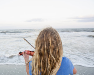 Rear view of Caucasian girl playing violin at beach