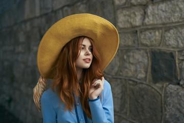 Woman wearing hat near stone wall