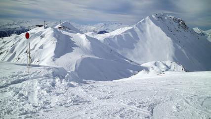 Ski, snowboard slopes on snowy mountain peaks in Les Arcs winter resort, Alps, France .
