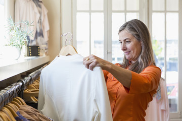 Caucasian woman shopping at clothing store