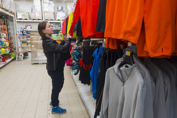 Caucasian woman examining shirt in store