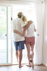 Caucasian couple hugging in patio doorway