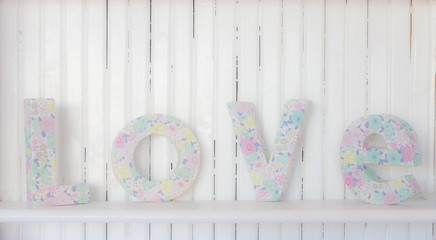 Flower decorated letters forming word LOVE on a shelf, wooden background, soft focus, High-key photo