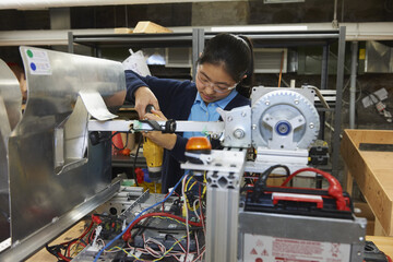 Chinese girl using drill in engineering workshop