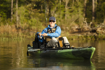 Caucasian man pedaling in kayak and fishing