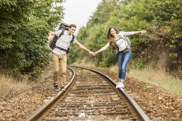 Caucasian couple balancing on train tracks