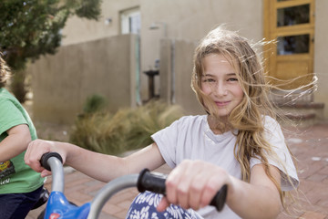 Wind blowing hair of Caucasian girl on bicycle