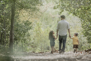 Hispanic father walking son and daughter in woods