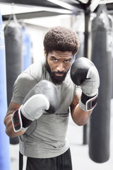 Portrait of Black man wearing boxing gloves in gymnasium