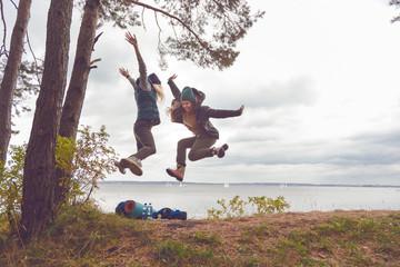 Happy travelers women jumping