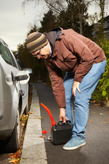 Man with plastic canister finished filling car tank on street