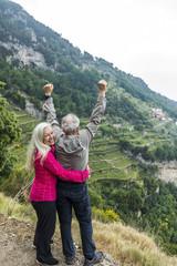 Caucasian couple celebrating on hill