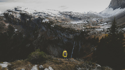 Young Caucasian female hiker in yellow raincoat wearing backpack enjoys view of a mountain waterfall in French Alps