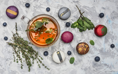 healthful hot herbal tea with berries, thyme and mint, appetizing, multicolored macaroons on a white rustic background, top view