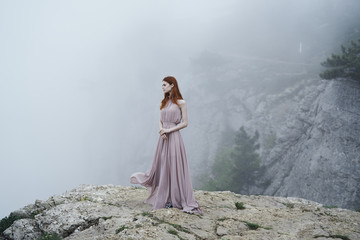 Caucasian woman wearing dress on rock in fog