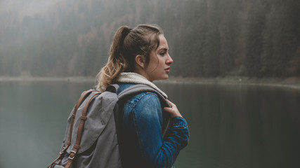 Attractive female hiker enjoys the view of lake Montriond in French Alps on a rainy day
