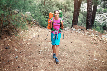 Woman hiker with backpack travelling in a pine forest by Lycian Way, Turkey