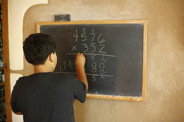 Native American boy solving equation on blackboard