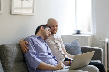 Caucasian men hugging on sofa and using laptop