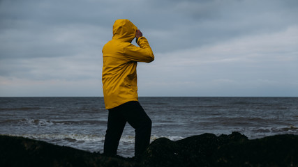 Adult Caucasian male in yellow raincoat enjoying the view of a sunset over the sea