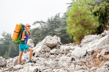 Happy young woman backpacker enjoy the fog view in wild forest with mist, Tahtali mountain in Turkey, travelling by Lycian Way concept