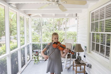 Caucasian girl playing violin on patio