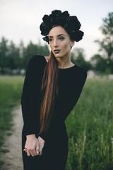 Middle Eastern woman wearing black dress on path in woods