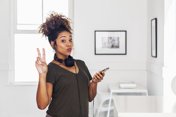 Mixed race woman holding cell phone gesturing peace