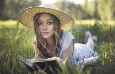 Portrait of woman lying in grass reading book
