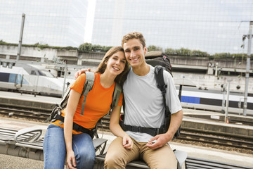 Caucasian couple waiting on bench at train station