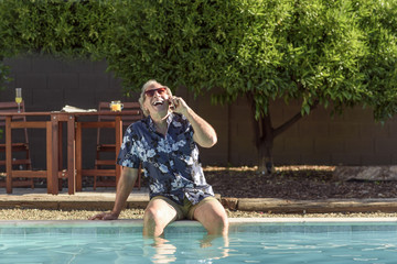 Caucasian man laughing on cell phone with legs in swimming pool