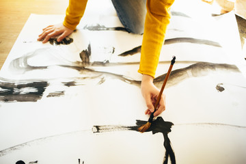 Female artist working in atelier. Painting on paper.
