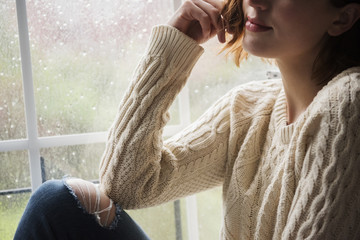 Portrait of pensive Caucasian woman near rainy window