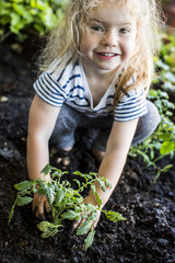 Portrait of girl posing with plant in garden
