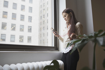 Young woman using smartphone while standing near window in office
