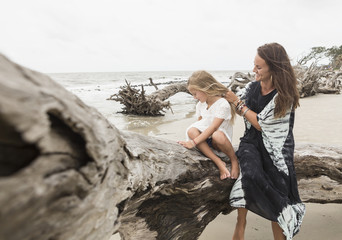 Caucasian mother and daughter sitting on driftwood on beach