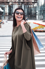 Successful shopping. Beautiful young woman in sunglasses holding shopping bags with smile while standing outdoors.