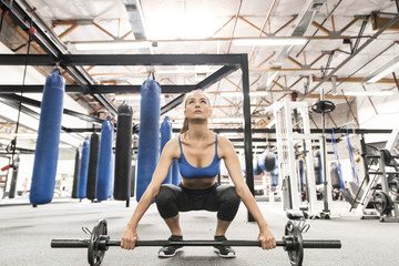 Mixed race woman crouching near barbell in gymnasium