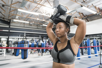 Black woman resting with arms raised in boxing ring